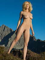 Stunning blonde babe naked on a mountain